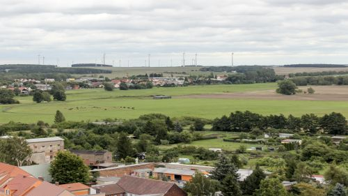 Siedlung mit Windenergieanlagen im Hintergrund