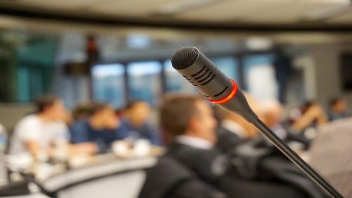 Konferenzteilnehmer, im Vordergrund ein Mikrofon